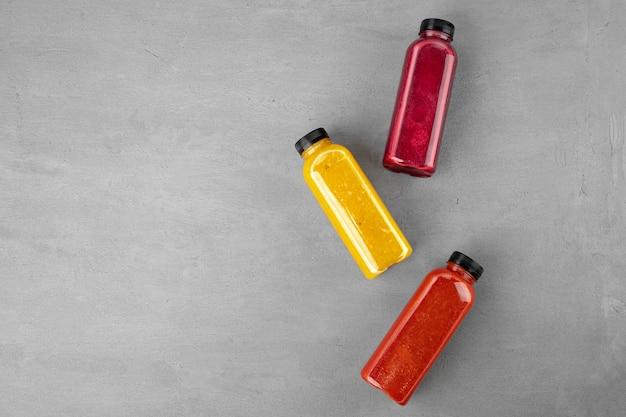 Drei plastikflaschen mit frisch gepresstem saft auf grau