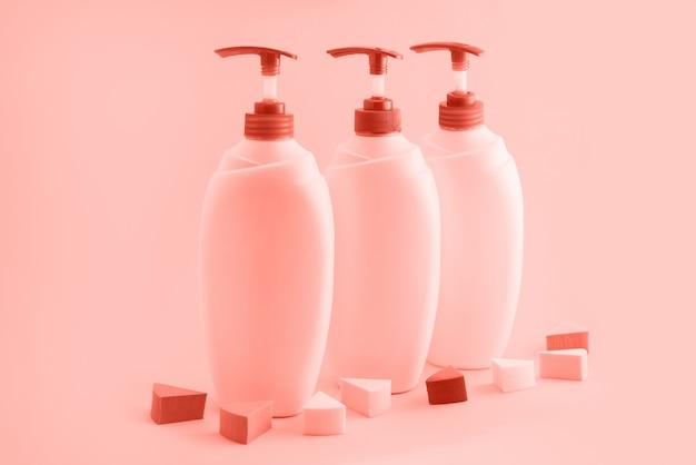 Drei plastikflaschen mit zufuhr auf korallenrotem hintergrund.