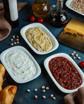 Drei platten mit türkischen beilagen werden im restaurant serviert