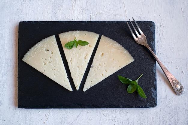 Drei portionen spanischer manchego cured cheese auf schiefer und von oben