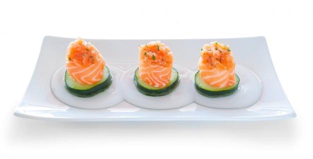Drei portionen sushi-lachs-gurken-füllung. auf einer platte.