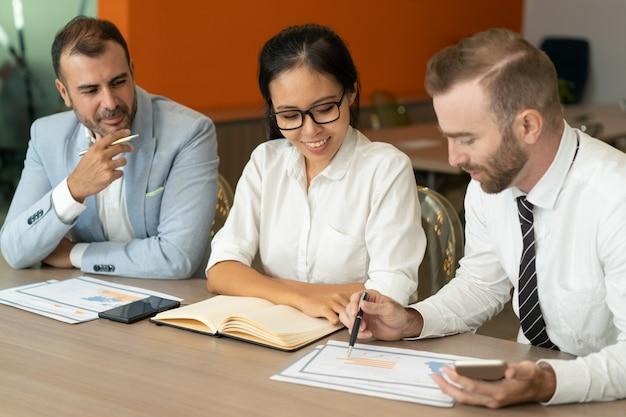 Drei positive geschäftsleute, die mit dokumenten am schreibtisch arbeiten