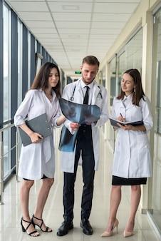Drei praktikanten untersuchen ein röntgenbild der lunge, um festzustellen, ob eine lungenentzündung durch das coronavirus vorliegt. medizinisches konzept