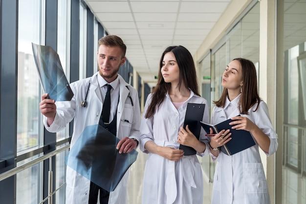 Drei praktikanten untersuchen eine röntgenaufnahme der lunge, um festzustellen, ob eine lungenentzündung durch das coronavirus vorliegt. medizinisches konzept