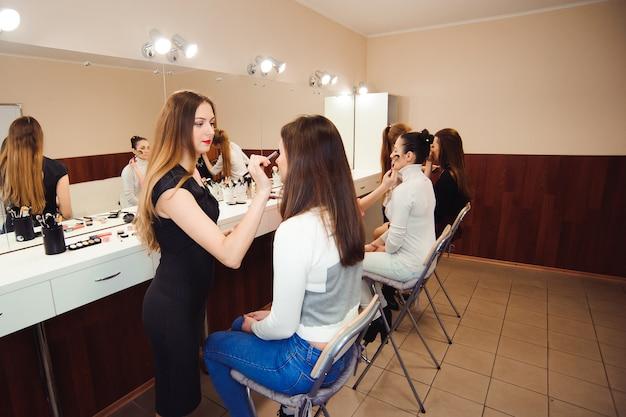 Drei professionelle visagisten arbeiten mit schönen jungen frauen. schule für professionelles make-up.
