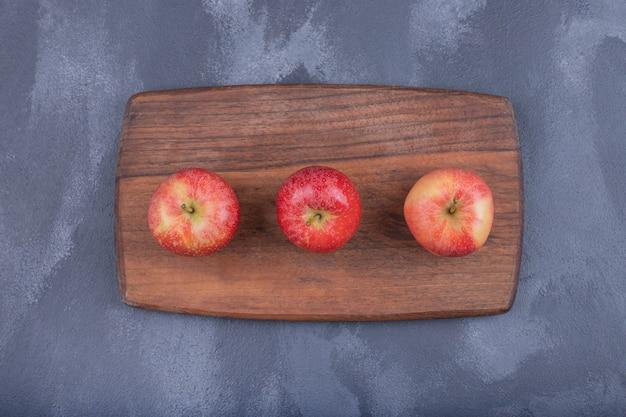 Drei reife äpfel auf holzbrett im dunkeln.