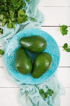 Drei reife avocados auf einem holztisch. gesundes lebensmittelkonzept. ansicht von oben