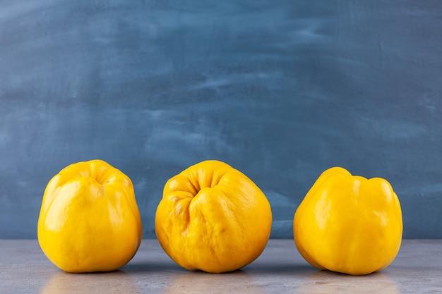 Drei reife gelbe quittenfrüchte auf steinhintergrund.