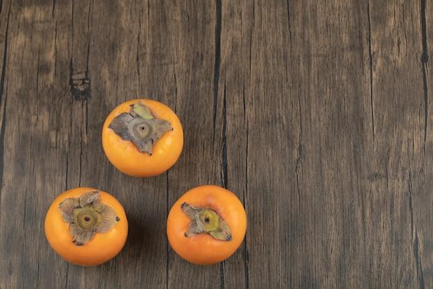 Drei reife kakifrüchte auf holzoberfläche gelegt