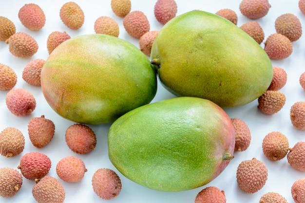 Drei reife mangos, umgeben von reifen litschi-früchten auf weißem hintergrund. tropische frucht.