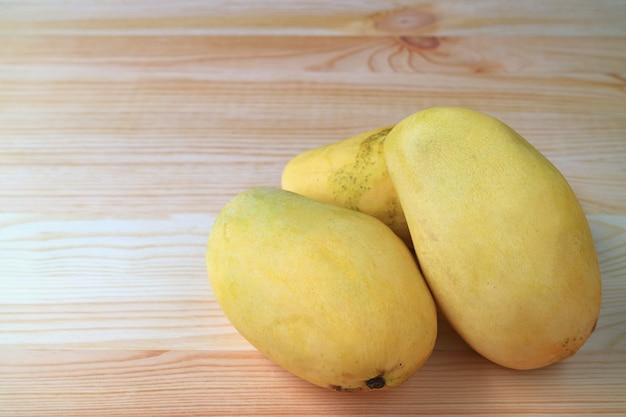 Drei reife ok-rong-mangos auf holztisch mit freiem platz