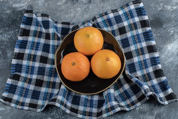 Drei reife orangen auf schwarzem teller mit tischdecke.