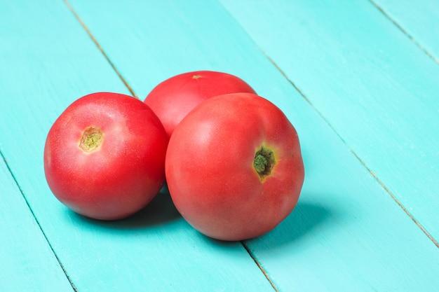 Drei reife tomaten auf einem blauen holztisch.