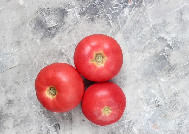 Drei reife tomaten auf einem grauen betonhintergrund.