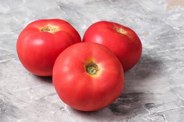 Drei reife tomaten auf einem grauen betontisch