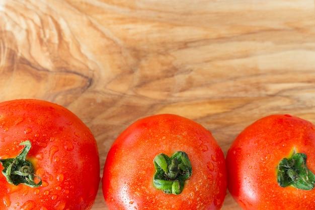 Drei reife tomaten mit wassertautropfen auf holz