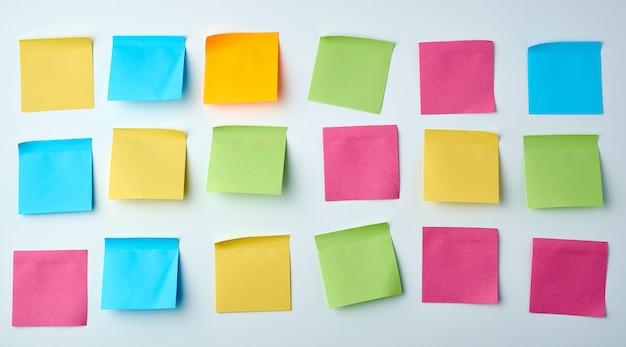 Drei reihen mehrfarbige aufkleber des leeren quadratischen papiers auf einer weißen wand