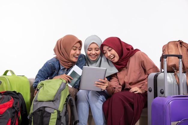 Drei reisende verschleierte frauen, die tabletten halten, während sie scherzhaft auf der couch sitzen