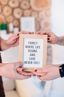 Drei reizende familienmitglieder halten gerahmtes bild. hochwertiges foto