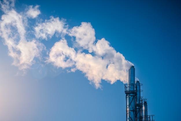 Drei rohre, die in einer reihe weißen rauch gegen einen blauen himmel rauchen.