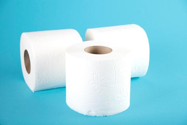 Drei rollen weißes toilettenpapier auf blau