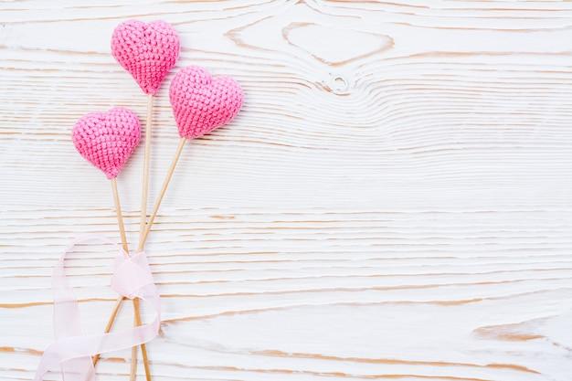 Drei rosa gestrickte herzen mit rosa band auf einem weißen hölzernen hintergrund
