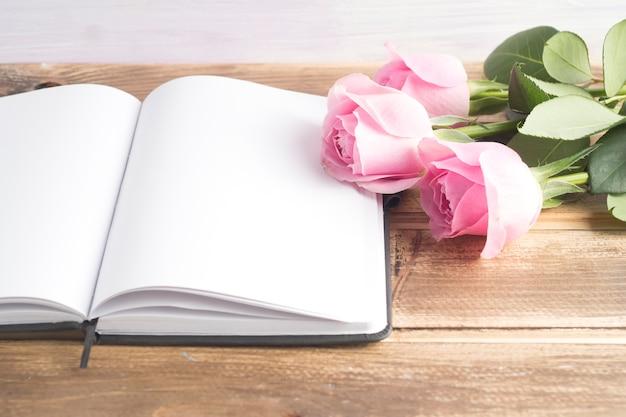 Drei rosa rosen mit einem offenen leeren tagebuch auf holztisch