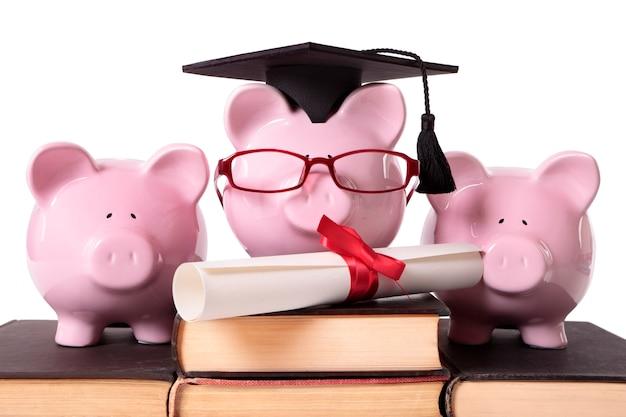 Drei rosa sparschweine auf einem stapel alten lehrbüchern