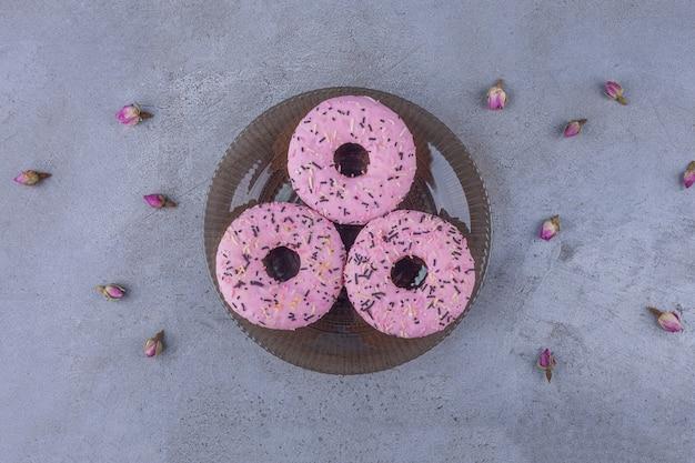 Drei rosa süße donuts mit knospenden rosen auf glasplatte.