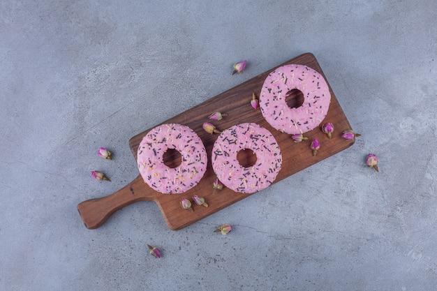 Drei rosa süße donuts mit knospenden rosen auf hölzernem schneidebrett.