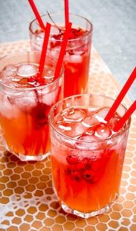 Drei rote cocktails mit eis und strohhalmen.