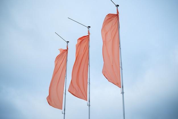 Drei rote fahnen am blauen himmel flattern im wind