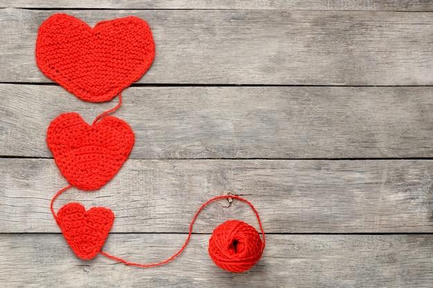 Drei rote gestrickte herzen, liebe und familie symbolisierend. familienbeziehung, bindungen.