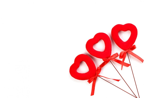 Drei rote herzen mit bögen auf einer weißen oberfläche