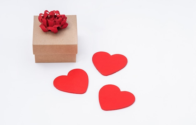 Drei rote herzen und eine geschenkbox mit einer roten schleife auf einem weißen hintergrund