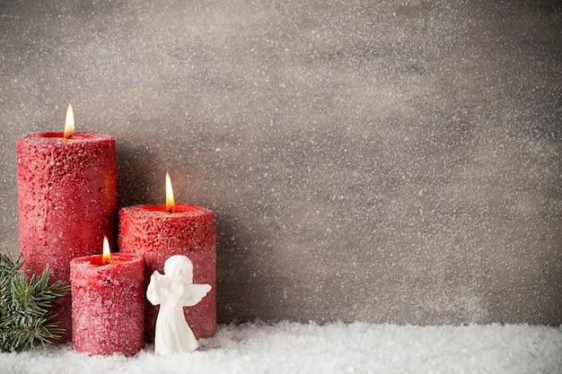 Drei rote kerzen auf grauem hintergrund, weihnachtsdekoration. adventsstimmung.