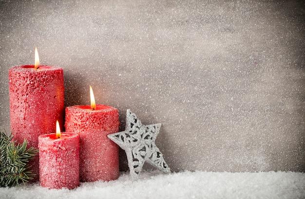 Drei rote kerzen auf grauer oberfläche, weihnachtsdekoration. adventsstimmung.