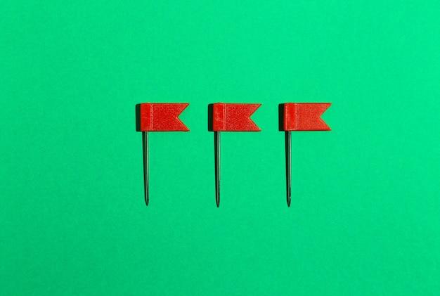 Drei rote kleine flaggenstifte auf grünem hintergrund. sicht von oben .