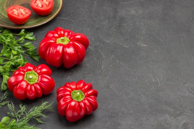 Drei rote paprika und petersilie und dill. platz kopieren. schwarzer hintergrund. ansicht von oben