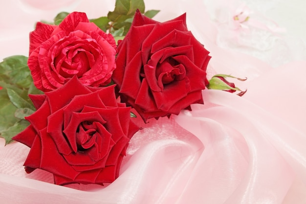 Drei rote rosen auf der rosa seide