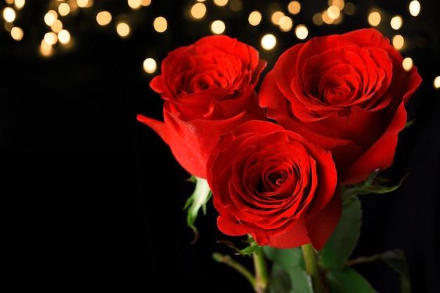 Drei rote rosen auf dunkler oberfläche