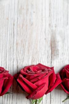 Drei rote rosen auf hellem hölzernem hintergrund mit kopienraum, draufsicht, vertikale zusammensetzung - bild