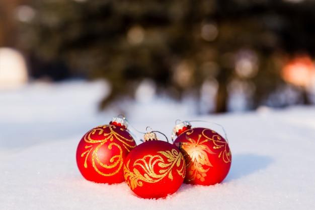 Drei rote weihnachtskugeln auf einem schnee. grußkarten-konzept des neuen jahres. textfreiraum