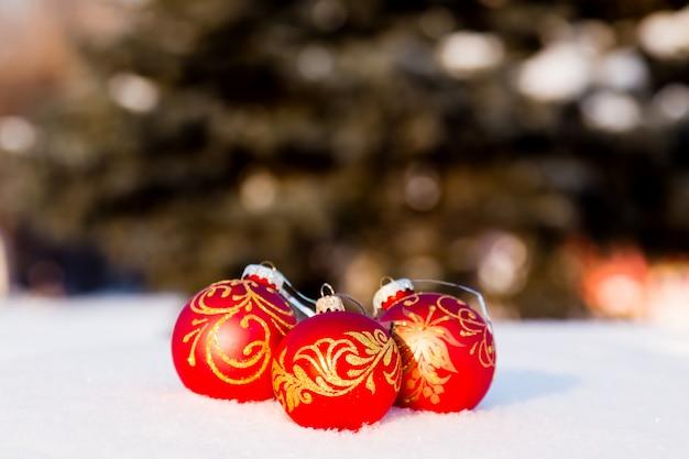 Drei rote weihnachtskugeln auf einem schnee