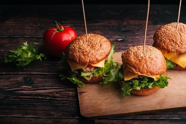 Drei saftige hamburger mit fleisch, käse, salat, tomate auf einem holzbrett
