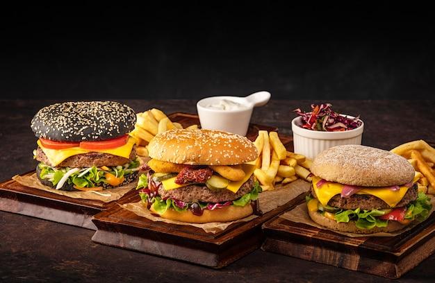 Drei saftige hausgemachte rindfleisch cheeseburger auf holzbrett. auswahl an burgern mit rindfleisch und käse im dunkeln