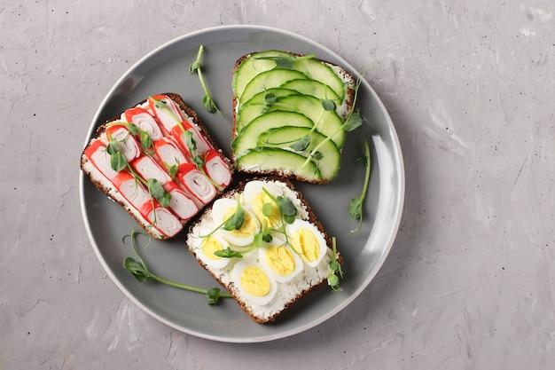 Drei sandwiches auf toast mit frischkäse, gurken, wachteleiern und krabbenstangen, verziert mit microgreen-erbsen