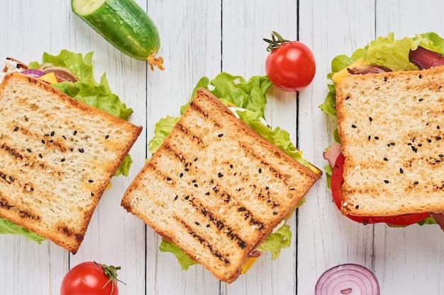 Drei sandwiches mit schinken, salat und frischem gemüse