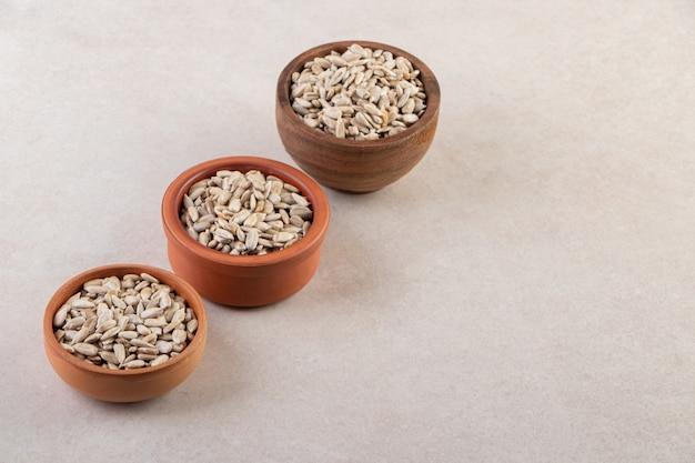 Drei schalen mit bio-sonnenblumenkernen auf steintisch.