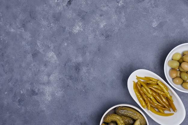 Drei schalen mit eingelegten gurken, paprika und oliven auf blauem grund.